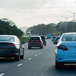 Traffic flowing on Caribbean island highway road. Vehicles drive on left hand side.